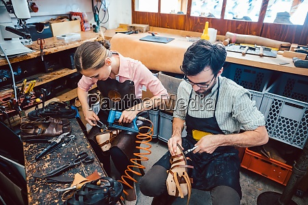 woman and man shoemaker working together