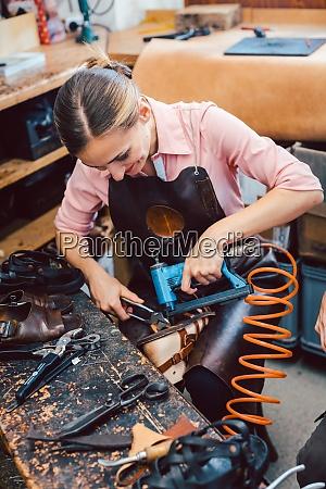 cobbler woman repairing a shoe