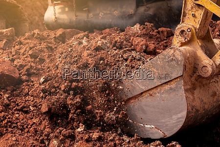 closeup bucket of backhoe digging the