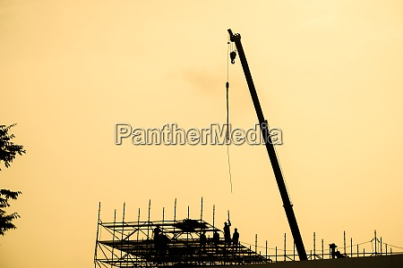 of large crane silhouette and sunset