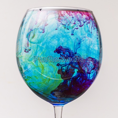 colorful ink drips into glass with