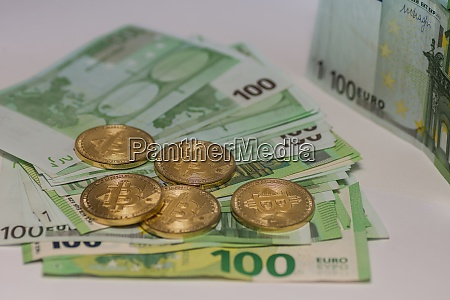 golden bitcoins lying on many 100