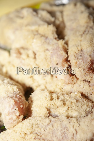 breaded and seasoned raw chicken breasts