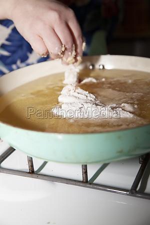 woman frying chicken strips