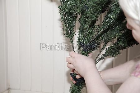 albino woman assembling an artificial christmas
