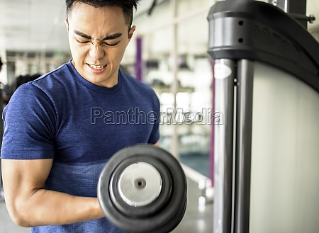 young man training with dumbbell in
