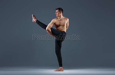 male yoga doing stretching exercise in