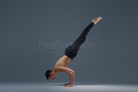 male yoga keeps balanc on hands