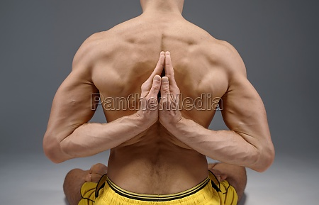 yoga sits with hands behind his