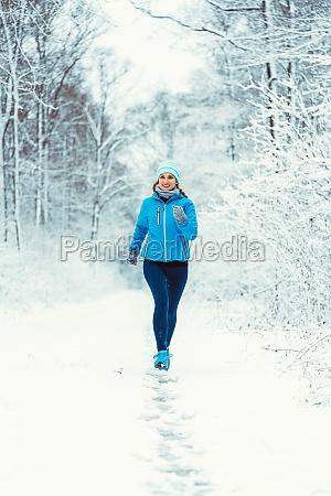 woman jogging towards camera in cold