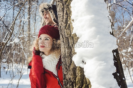 playful couple hiding behind a tree