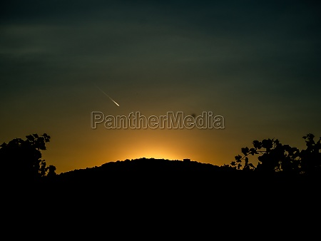 sunset behind hills and bushes