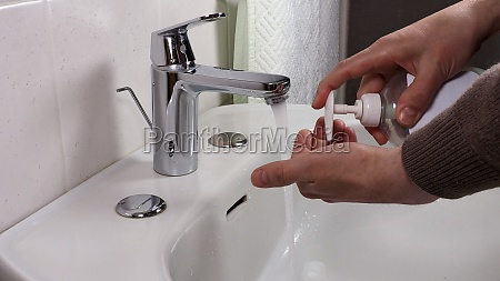 unrecognisable person washing hands