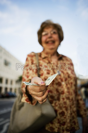 senior woman holding a twenty dollar