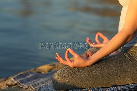 woman hands at sunset practicing yoga