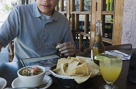 man eating at outdoor restaurant