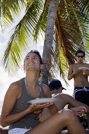 young woman eating at beach party