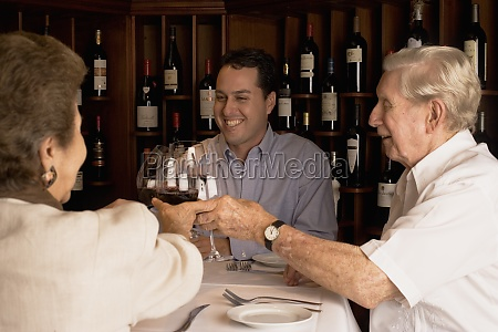 family toasting wine in restaurant