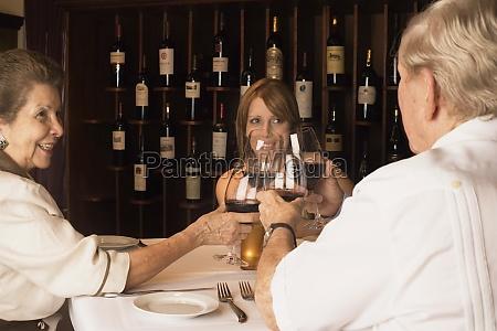 family toasting wine in restaurant