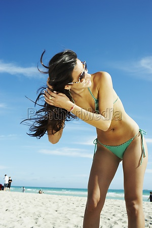 young woman shaking hair on beach