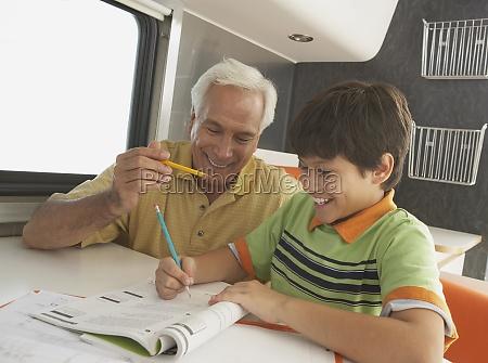 senior man teaching his grandson and