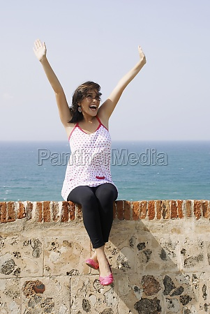 young woman sitting on the ledge