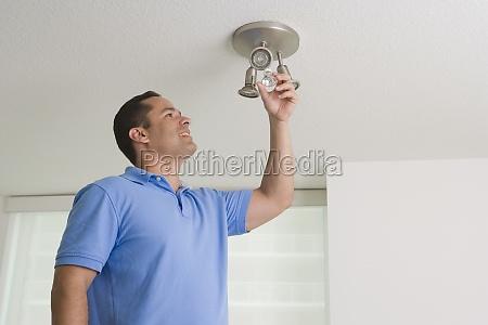 man checking a light bulb