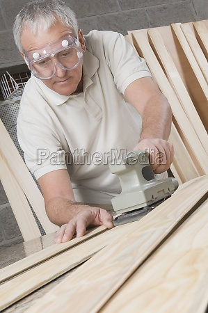 carpenter planing a wooden plank