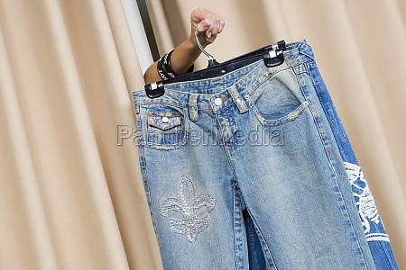persons hand showing a jeans through