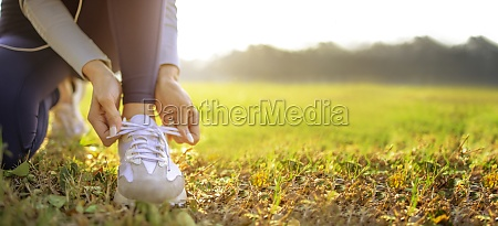 young woman runner tying her shoes