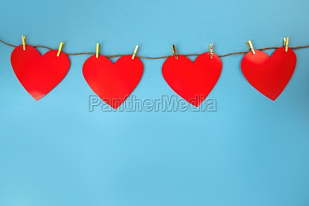 four red hearts hanging on cord