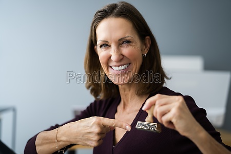 happy woman pointing at approved stamp