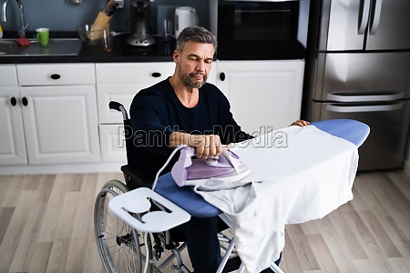 handicapped disabled man in wheelchair ironing