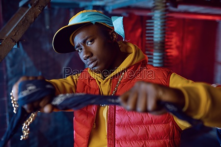 stylish rapper in yellow hoodie posing