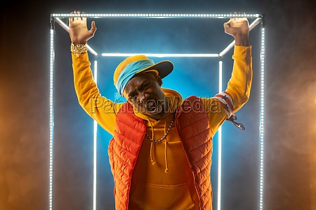 young stylish rapper poses in illuminated