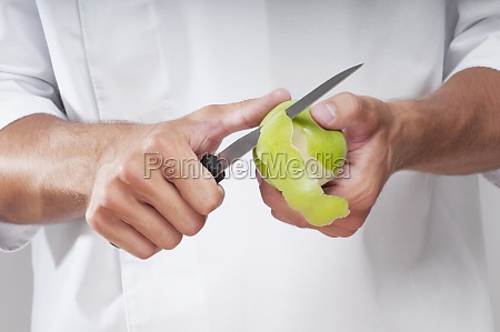 man peeling a granny smith apple