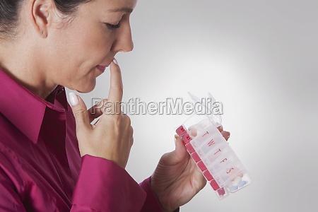 woman looking at a pill box