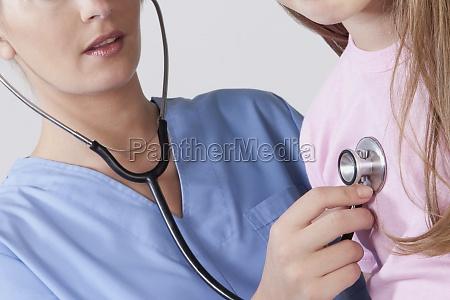 female nurse examining a girl with