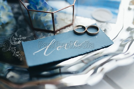 wedding rings at wedding invitation with