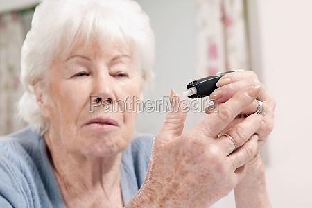 woman testing her blood sugar level