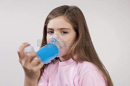 girl using an asthma inhaler attached