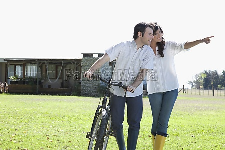 couple walking with a bicycle and