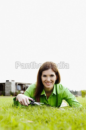 woman trimming grass with scissors