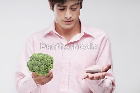 man choosing between broccoli and chocolate
