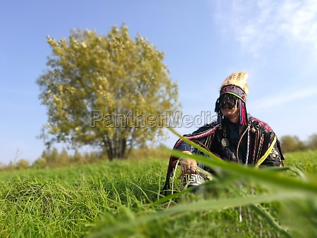 young shaman sits on a lawn
