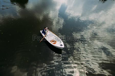 newlyweds on white boat swim in
