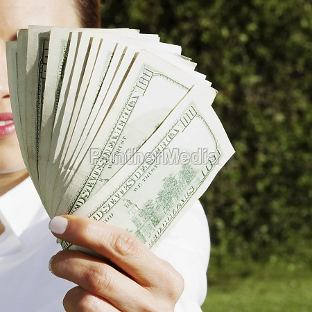 businesswoman holding currency note