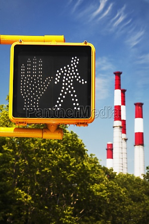 crosswalk signal with smoke stacks in