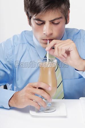 closeup of a businessman drinking milkshake