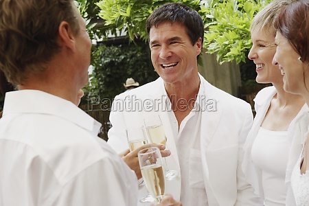 two mature couples celebrating with champagne